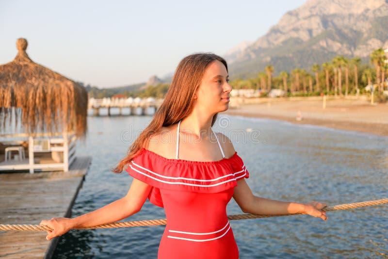 Het aantrekkelijke jonge meisje in rood zwempak bevindt zich op overzeese strandachtergrond stock foto