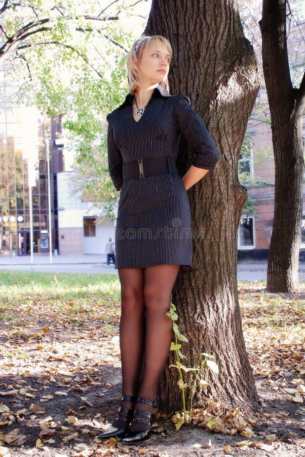 Het aantrekkelijke jonge meisje verbergen achter de boom stock fotografie