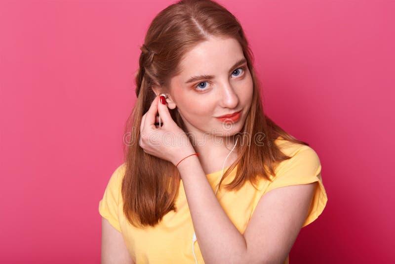 Het aantrekkelijke jonge meisje zet oortelefoons, klaar om aan muziek te luisteren, bekijkt derictly camera, draagt heldere gele  royalty-vrije stock foto