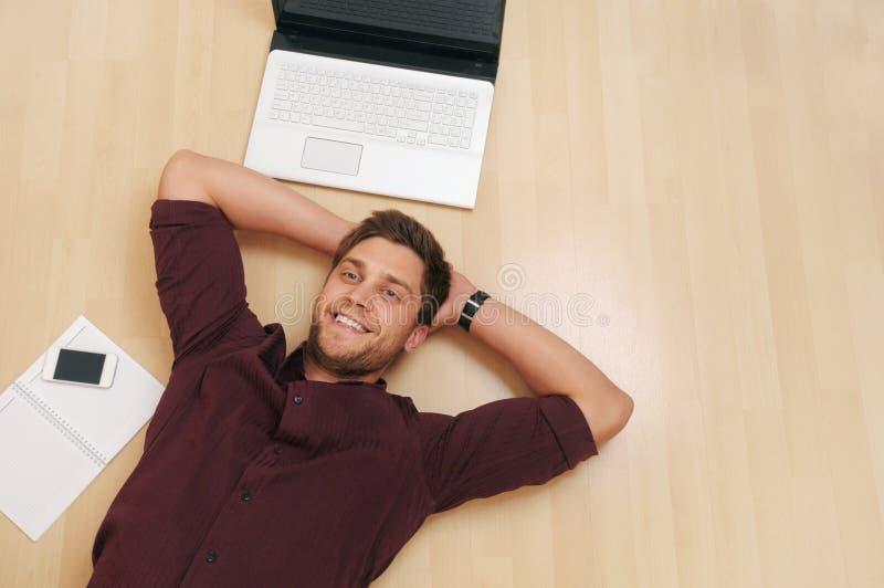 Het aantrekkelijke jonge mens ontspannen op de houten vloer thuis royalty-vrije stock foto