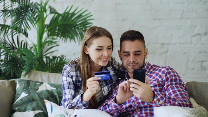 Het aantrekkelijke jonge paar met smartphone en de creditcard die op Internet winkelen zitten thuis op laag in woonkamer royalty-vrije stock fotografie
