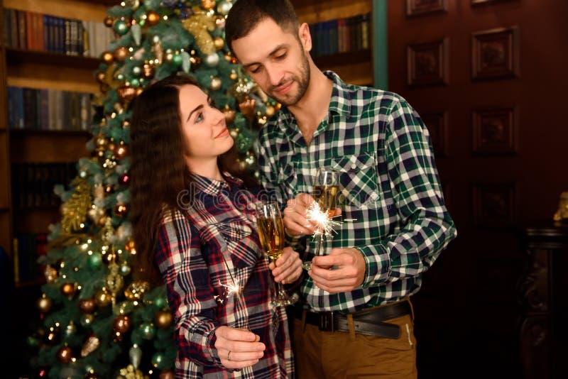 Het aantrekkelijke jonge paar is het vieren thuis samen vakantie, het drinken van champagne en het glimlachen met binnen de licht stock foto