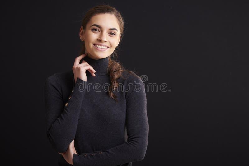 Het aantrekkelijke jonge portret van de vrouwenstudio terwijl status bij donkere achtergrond royalty-vrije stock foto