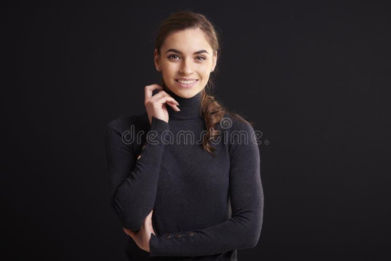 Het aantrekkelijke jonge portret van de vrouwenstudio terwijl status bij donkere achtergrond royalty-vrije stock fotografie