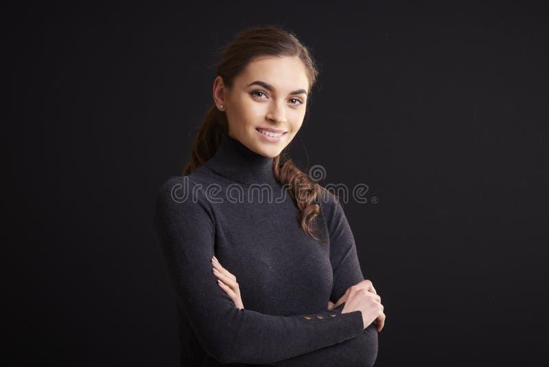 Het aantrekkelijke jonge portret van de vrouwenstudio terwijl status bij donkere achtergrond royalty-vrije stock foto's