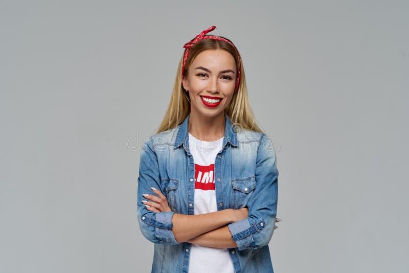 Het aantrekkelijke jonge vrouw glimlachen ruim vouwde haar handen op haar het denimoverhemd en t-shirt van de borst vrijetijdskle stock fotografie