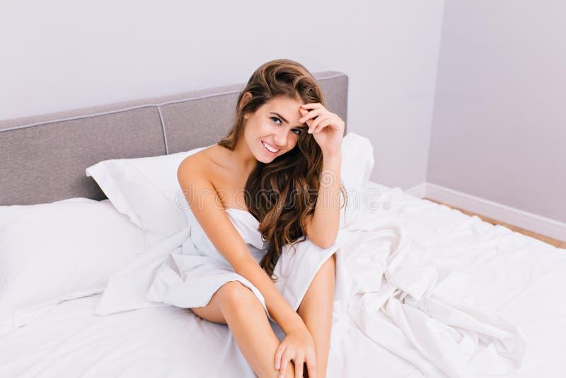 Het aantrekkelijke jonge vrouw koelen in bed in moderne flat Blij verbazend glimlachend meisje met het lange donkerbruine haar on stock foto's