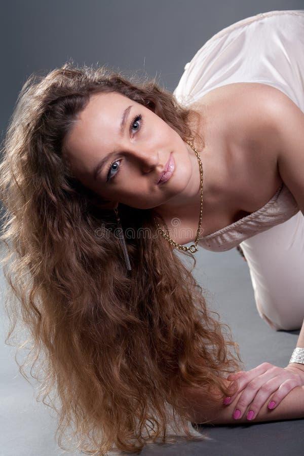 Het aantrekkelijke jonge vrouw stellen op studiovloer royalty-vrije stock afbeeldingen