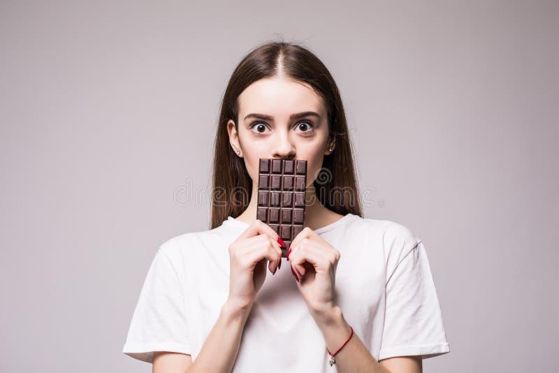 Het aantrekkelijke Jonge Vrouw Verbergen achter een Chocoladereep Het concept van de gezondheid stock foto