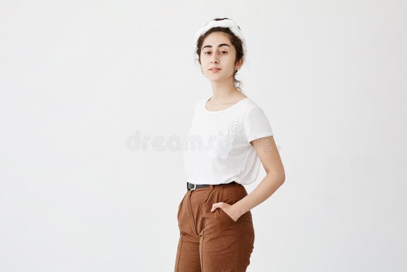Het aantrekkelijke jonge vrouwelijke model met donker en golvend haar in broodje, die witte t-shirt en broeken dragen, die haar h stock afbeelding