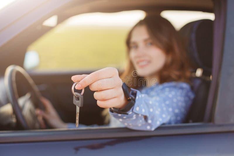 Het aantrekkelijke jonge wijfje houdt autosleutels, die gelukkige eigenaar van nieuwe automobiele, vage achtergrond zijn De mooie stock afbeelding