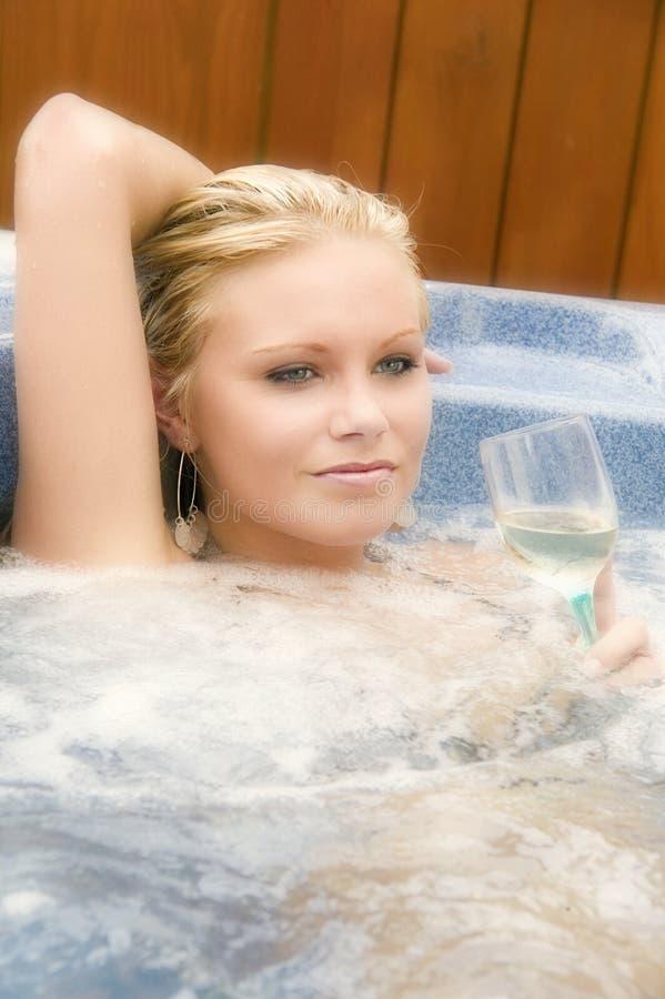Het aantrekkelijke jonge woamn ontspannen in een Jacuzzi royalty-vrije stock afbeelding