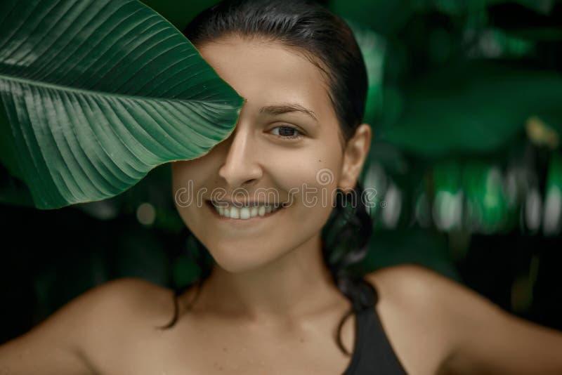 Het aantrekkelijke Kaukasische donkerbruin meisje model stellen in een pool met groene installaties Schoonheidsmiddelen reclame stock afbeeldingen