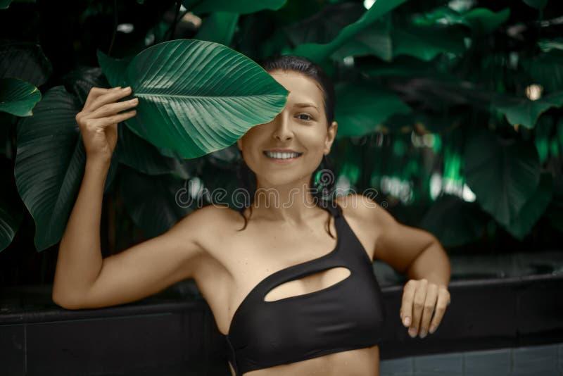 Het aantrekkelijke Kaukasische donkerbruin meisje model stellen in een pool met groene installaties Schoonheidsmiddelen reclame stock afbeelding