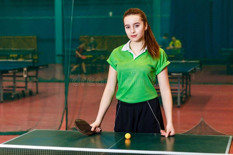 Het aantrekkelijke Kaukasische tienermeisje bevindt zich dichtbij het pingpong en bekijkt de camera Jonge sportvrouw stock afbeelding