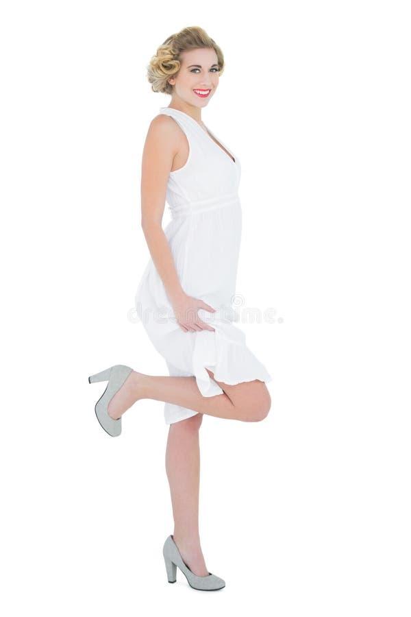 Het aantrekkelijke manierblonde model stellen met een omhoog been royalty-vrije stock fotografie