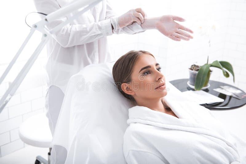 Het aantrekkelijke meisje liggen daybed terwijl cosmetologist die op beschermende handschoenen zetten stock afbeelding