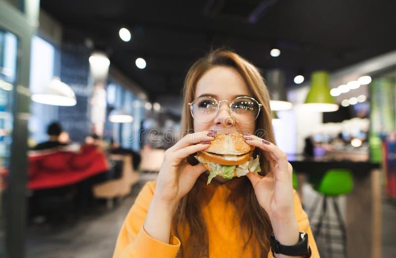 Het aantrekkelijke meisje in oranje kleren en glazen zit in een fast-food restaurant en eet een grote smakelijke hamburger royalty-vrije stock foto's