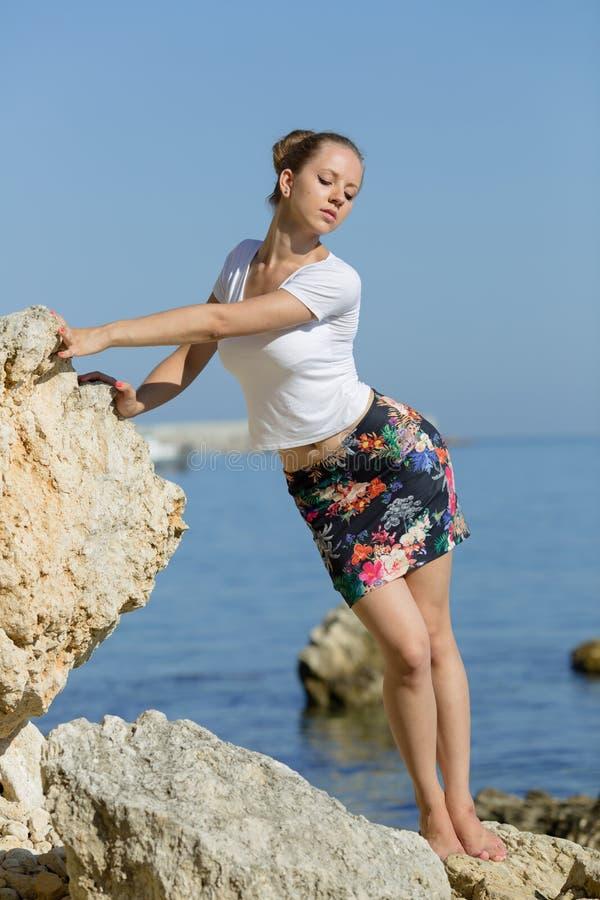 Het aantrekkelijke meisje stellen die op handen op rotsachtige kust leunen royalty-vrije stock foto