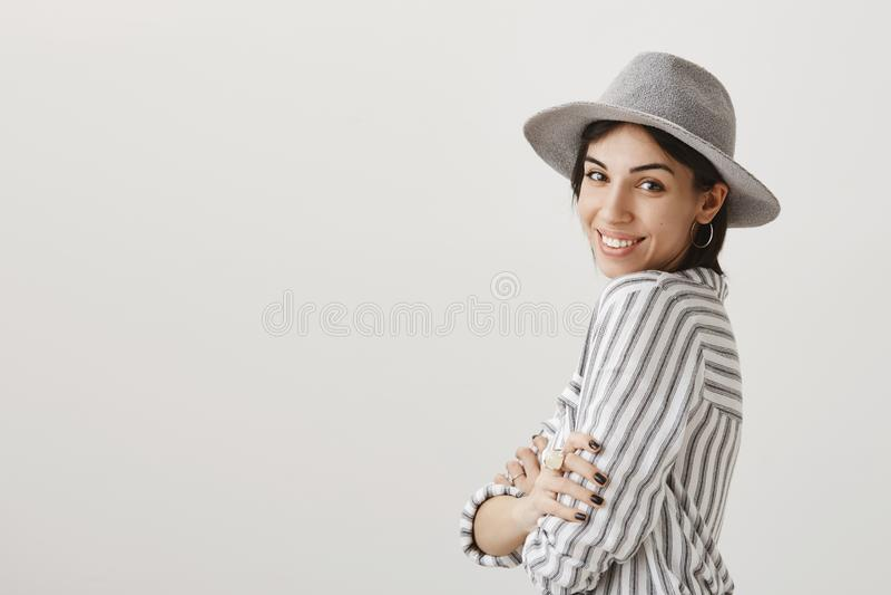 Het aantrekkelijke meisje stellen om nieuw beeld op vakantie te maken Modieus Kaukasisch meisje in modieuze hoed die zich binnen  royalty-vrije stock afbeeldingen