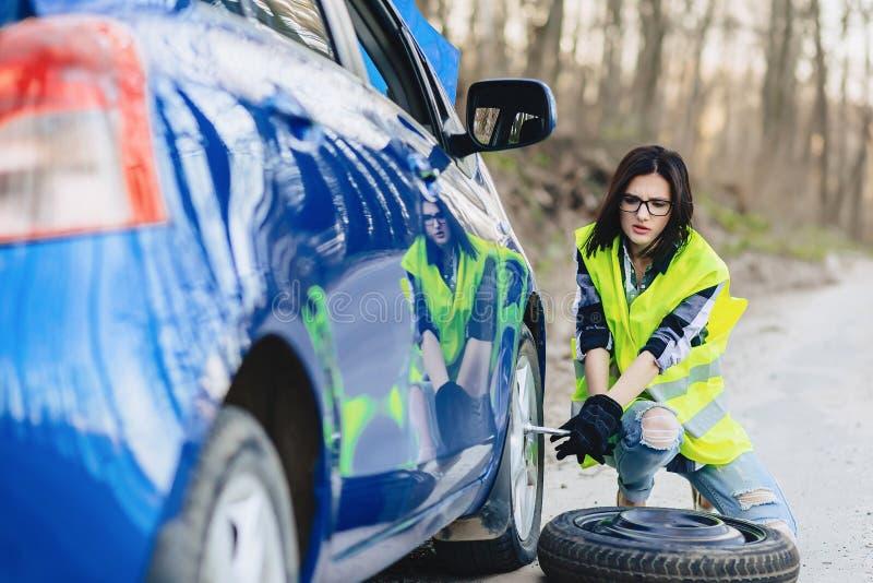 het aantrekkelijke meisje verwijdert wiel uit auto bij alleen weg royalty-vrije stock foto's