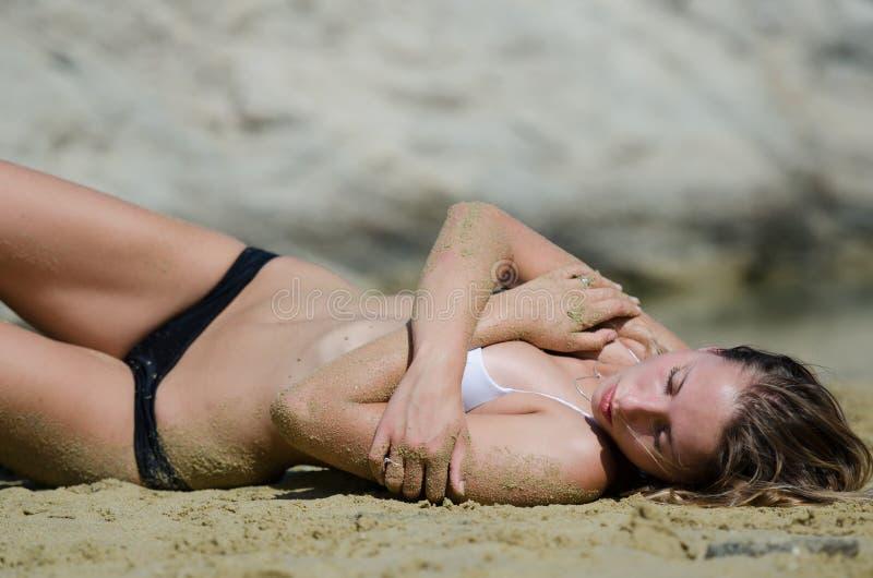 Het aantrekkelijke model met bikini op het zand in aantal van het interesseren stelt royalty-vrije stock fotografie