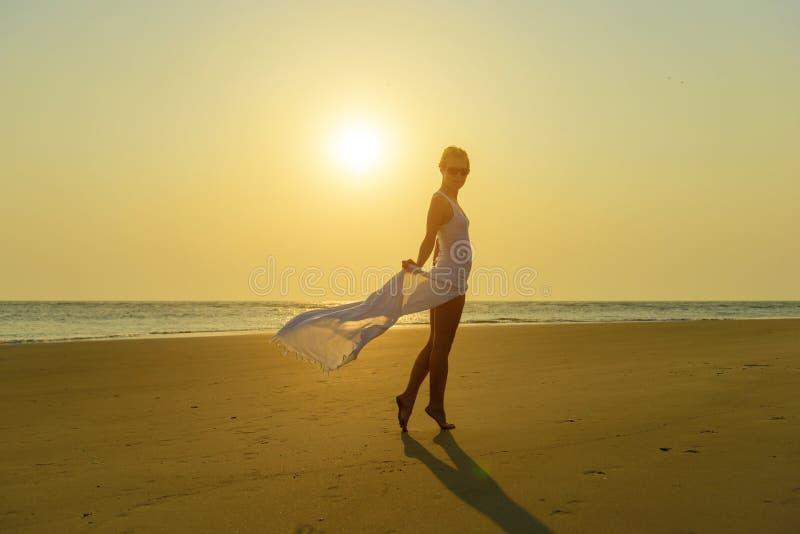 Het aantrekkelijke modieuze blonde in zonnebril en lichte witte kleding bevindt zich blootvoets op geel zand op achtergrond van o royalty-vrije stock foto