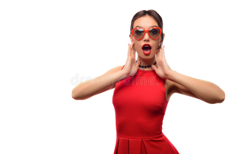 Het aantrekkelijke mooie meisje in rode kleding en zonnebril in de vorm van harten is open mond met verrassing stock foto's