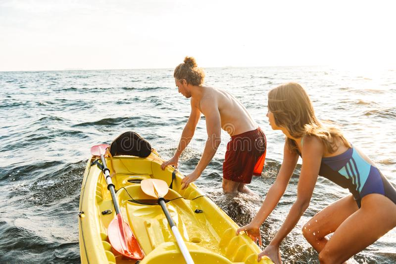 Het aantrekkelijke paar kayaking op overzees samen stock afbeelding