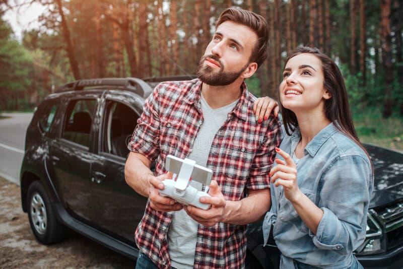 Het aantrekkelijke paar verenigt zich en kijkt omhoog Zij zijn ouside in park Er is een auto achter hen De kerel is royalty-vrije stock fotografie