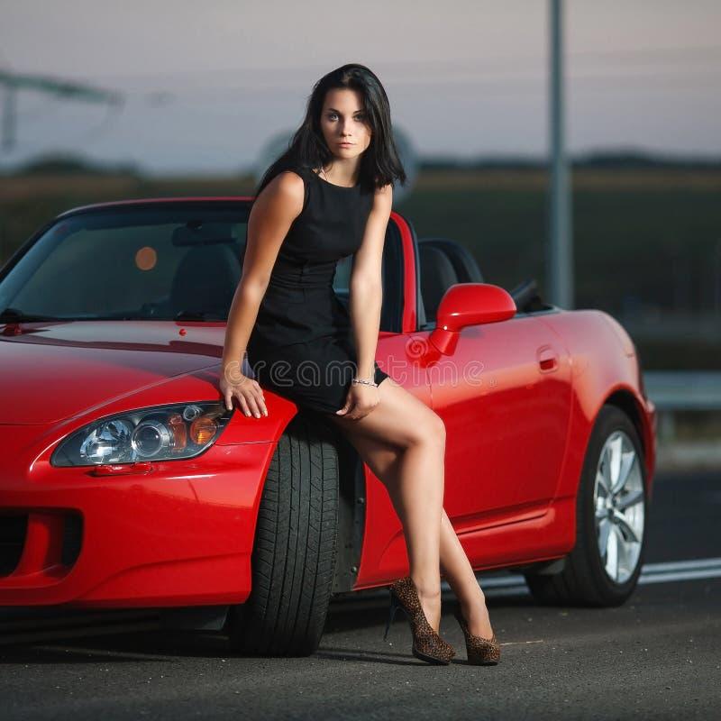 Het aantrekkelijke portret van de schoonheids sexy vrouw met auto stock foto