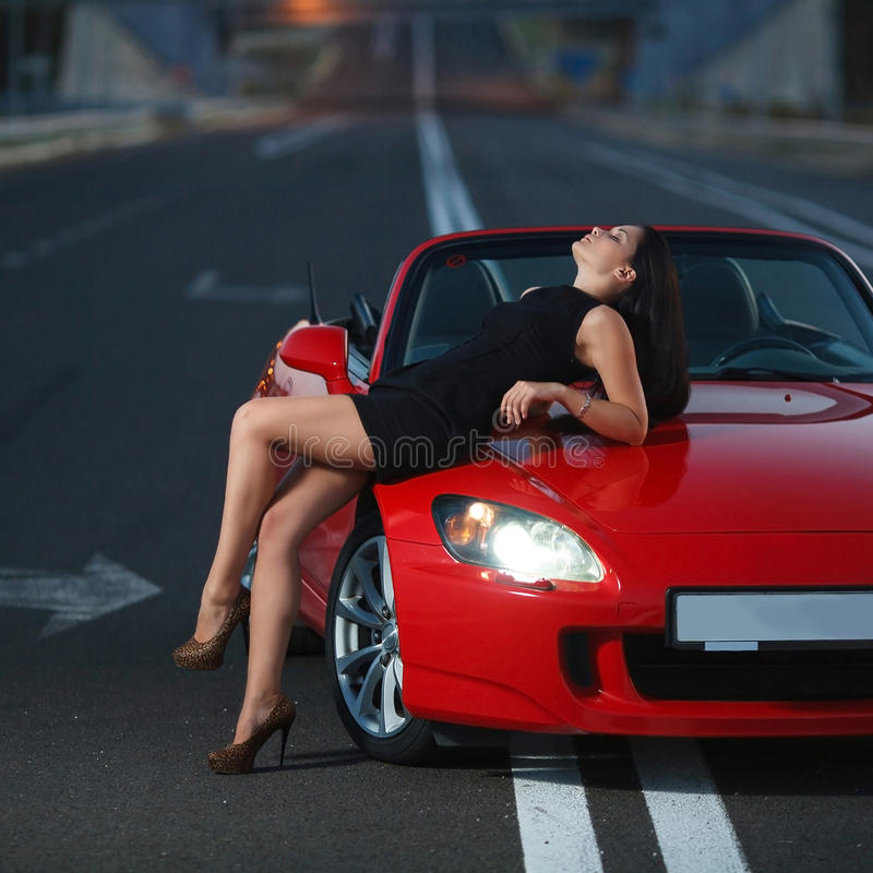 Het aantrekkelijke portret van de schoonheids sexy vrouw met auto stock afbeelding