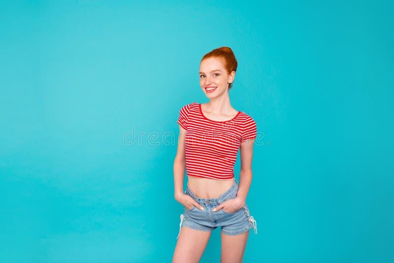 Het aantrekkelijke positieve magere vrolijke roodharige meisje van Nice met bu royalty-vrije stock fotografie