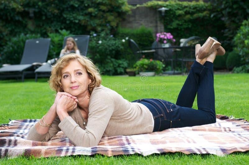Het aantrekkelijke rijpe vrouw ontspannen in tuin stock afbeelding