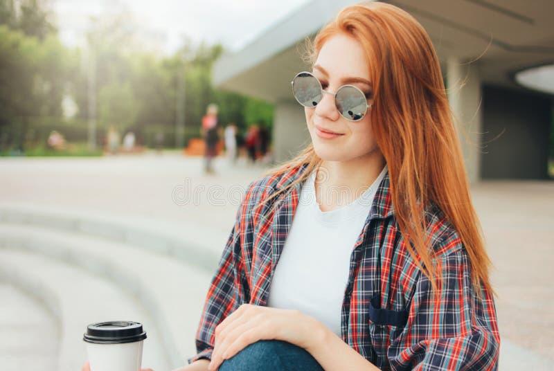 Het aantrekkelijke roodharige glimlachende meisje in ronde zonnebril met kop van koffie om binnen te gaan dient vrijetijdskleding stock afbeeldingen