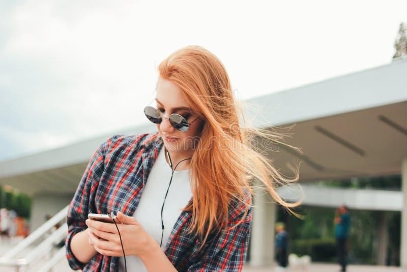 Het aantrekkelijke roodharige glimlachende meisje in ronde zonnebril met telefoon in haar dient vrijetijdskleding het luisteren m stock afbeeldingen