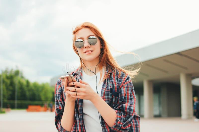 Het aantrekkelijke roodharige glimlachende meisje in ronde zonnebril met telefoon in haar dient vrijetijdskleding het luisteren m royalty-vrije stock foto
