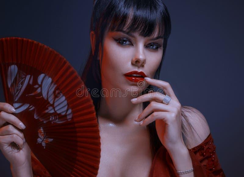 Het aantrekkelijke sexy meisje met donker zwart haar, grijze ogen, het verbazen make-up met rode lippen bekijkt speels de camera royalty-vrije stock foto