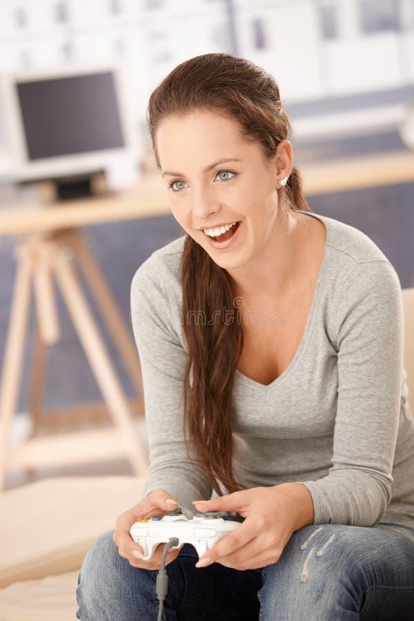 Het aantrekkelijke spel van de meisjes speelcomputer thuis royalty-vrije stock afbeelding
