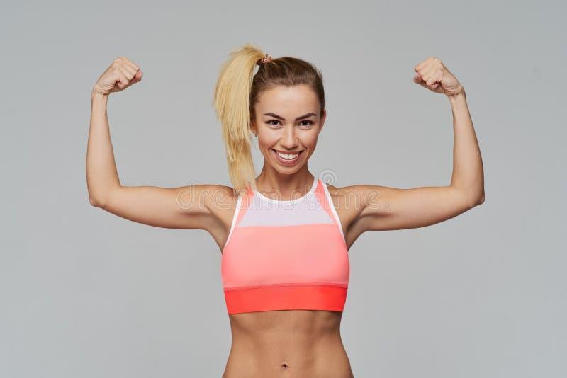 Het aantrekkelijke sportieve het glimlachen vrouw stellen voor een Studioportret op grijze achtergrond De positieve emoties en be stock fotografie