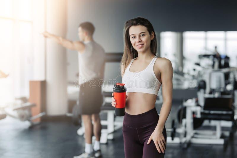 Het aantrekkelijke sportmeisje glimlachen en drinkwater terwijl status bij de gymnastiek met de jongen die op achtergrond opleidt stock fotografie