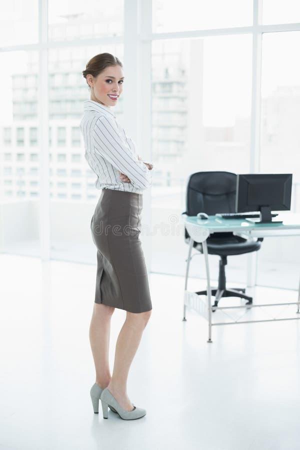 Het aantrekkelijke vreedzame onderneemster stellen die zich in haar bureau bevinden stock afbeeldingen