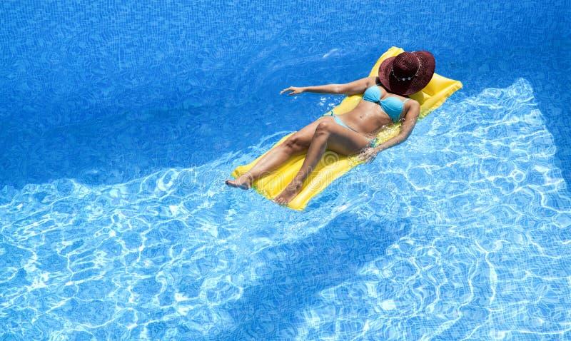 Het aantrekkelijke vrouw ontspannen op luchtbed stock afbeeldingen