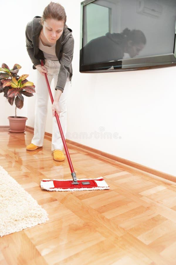 Het aantrekkelijke vrouw schoonmaken in haar huis royalty-vrije stock afbeelding