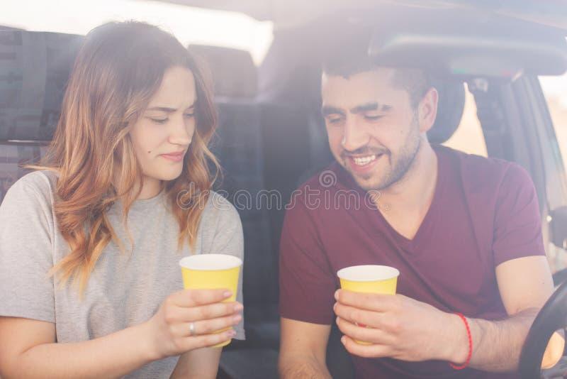 Het aantrekkelijke vrouwelijke en ongeschoren mannelijke paar heeft koffiepauze in auto, bereikt bestemming met hoge snelheid De  stock foto's