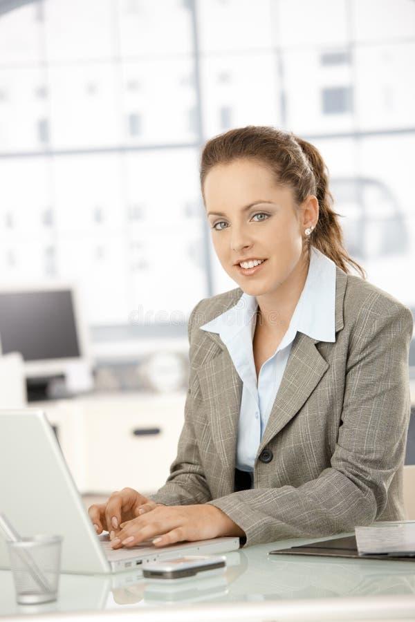 Het aantrekkelijke vrouwelijke werken aan laptop in bureau royalty-vrije stock afbeeldingen
