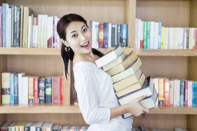 Het aantrekkelijke wijfje brengt stapel boeken in bibliotheek royalty-vrije stock afbeelding