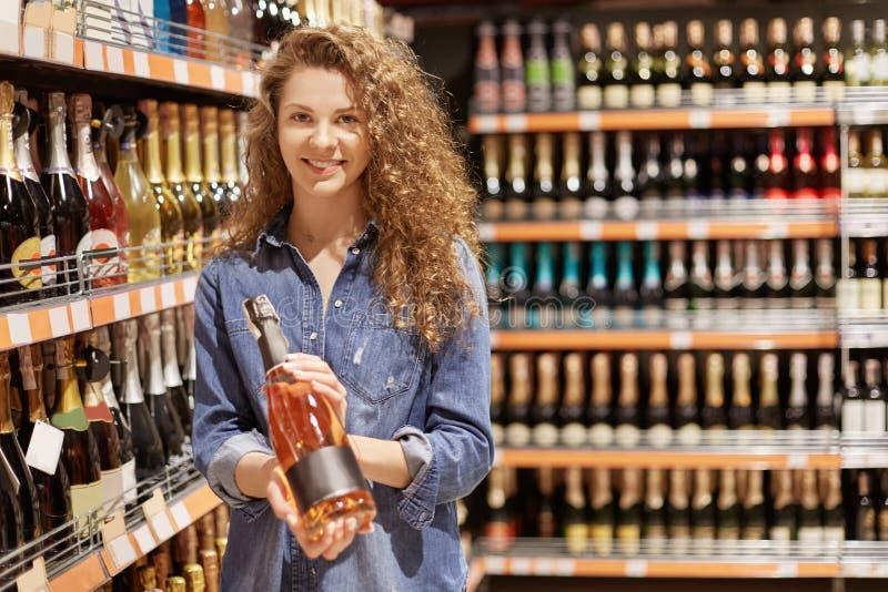 Het aantrekkelijke wijfje met opgetogen blik, houdt fles van alcoholische drank, kiest drank in supermarkt, die in goede stemming royalty-vrije stock afbeeldingen