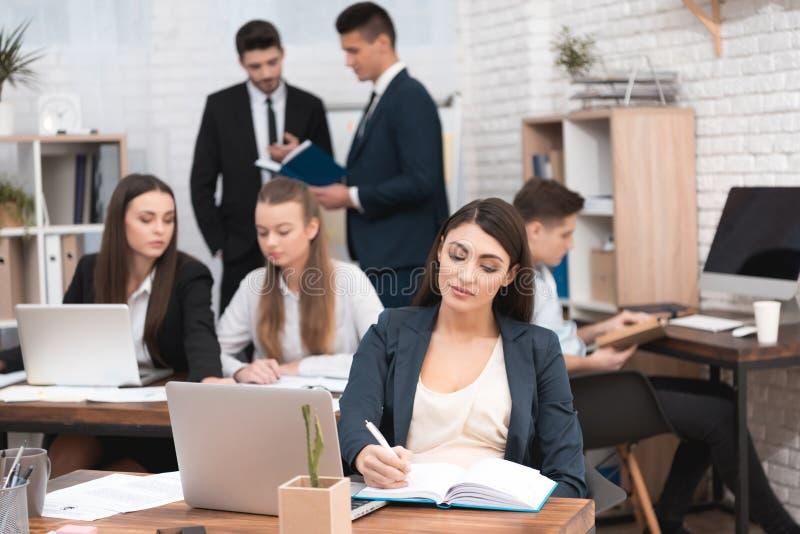 Het aantrekkelijke zwangere meisje werkt in bureau met collega's Zwangere onderneemster in werkruimte moederschap royalty-vrije stock foto