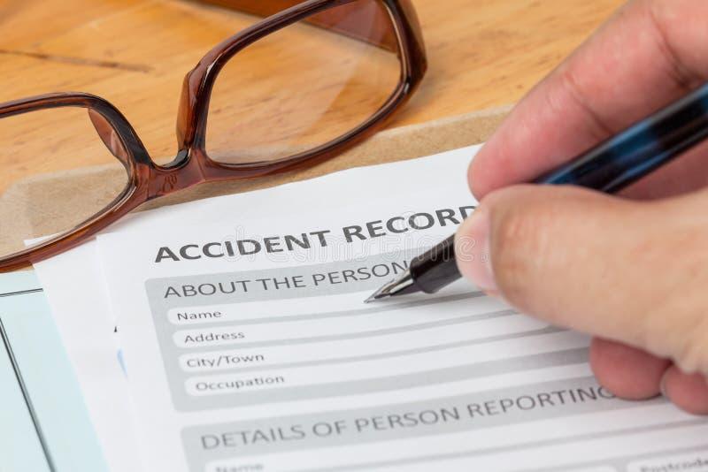 Het aanvraagformulier van het ongevallenrapport en menselijke hand met pen op brow stock afbeeldingen
